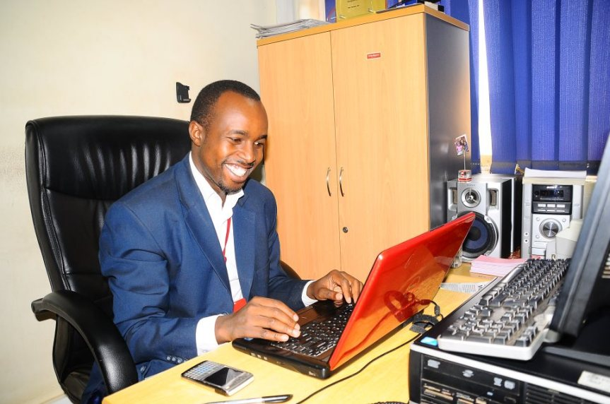 Njoroge smiles on the job at the desk of then news editor Alex B. Atuhaire. Facebook photo.